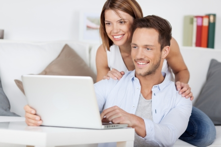laptop stand: Cheerful couple searching something on laptop at home