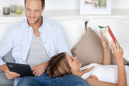 Beautiful couple reading using book and digital computer in the living room photo