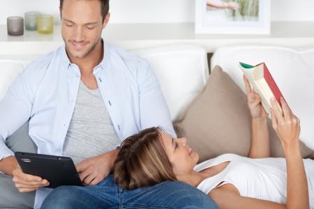 mujer leyendo libro: Hermosa pareja lectura con libros y ordenador digital en la sala de estar
