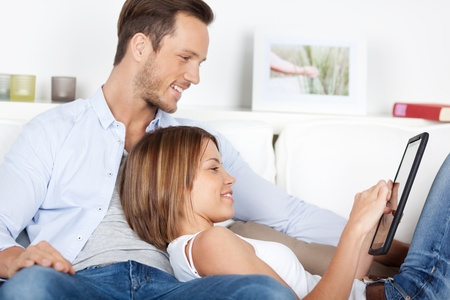 Portrait of sweet couple playing using digital tablet in living room photo
