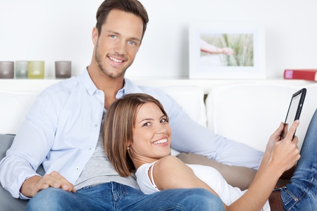 Portrait of husband and wife browsing through digital tablet in living room photo