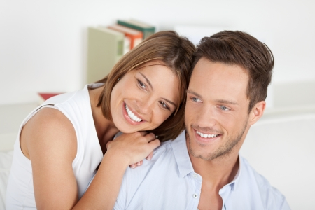 young couple smiling: Happy young couple looking at something in the living room