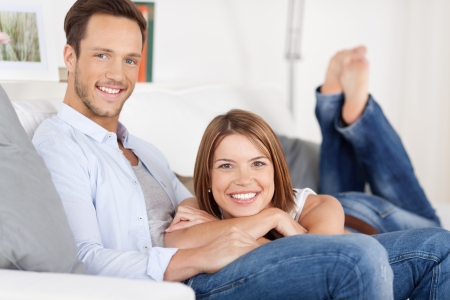lovely couple: Beautiful smiling couple relaxing in sofa at home