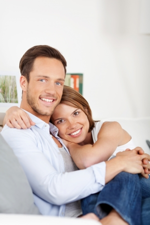passionate lovers: Portrait of couple sitting on couch and cuddling at home Stock Photo