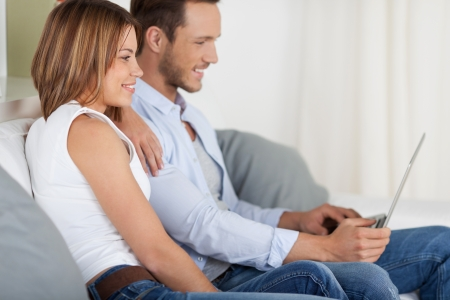 Attractive young couple playing through digital tablet on the couch Stock Photo - 21162459