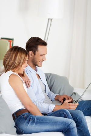 Happy attractive couple browsing on laptop at home Stock Photo - 21162460