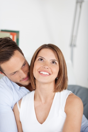 woman neck: Young couple cuddling on couch in living room Stock Photo