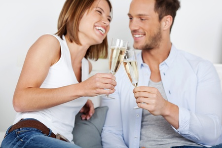 woman drinking wine: Laughing young couple dating with champagne at home