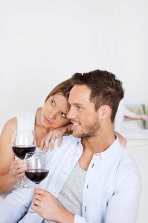 In love couple sitting on sofa and drinking red wine photo
