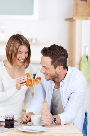 Laughing couple eating croissant in the kitchen photo