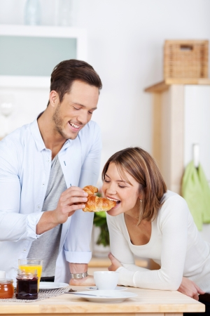 Man is feeding his girlfriend a croissant for breakfast photo