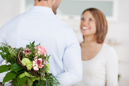 Young man hides a bouquet of flowers behind his back photo