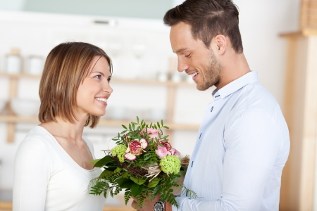 gives: Young man gives flowers to his girlfriend Stock Photo