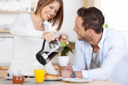 Young woman is pouring her boyfriend a coffee photo