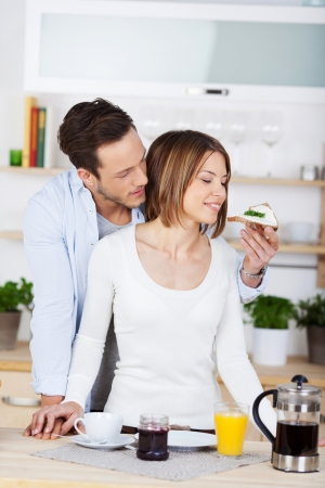 Young man feeding his girlfriend a slice of buttered bread photo