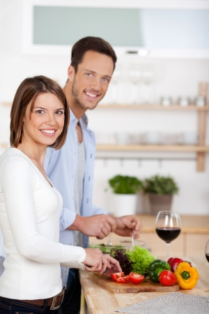 Portrait of lovely couple cooking in their kitchen photo