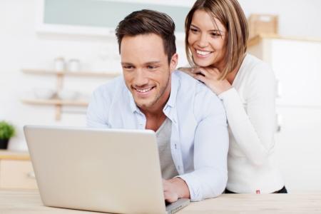 Lachen paar surfen op het internet op de laptop