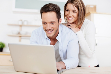 online shopping: Laughing couple browsing the internet at the laptop Stock Photo