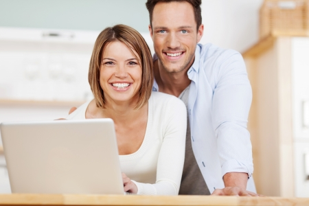 Happy couple browsing the internet at the laptop Stock Photo - 21162516