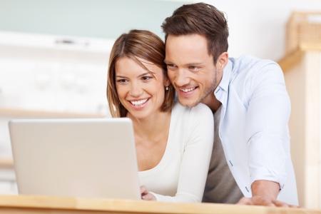 집에서 노트북에 근무하는 아름 다운 부부를 닫습니다