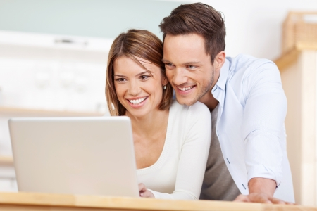 Close up beautiful couple working on laptop at home photo
