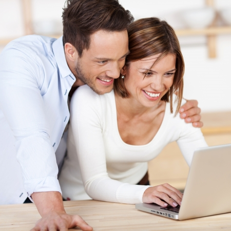 Sweet happy couple browsing the internet at the laptop photo
