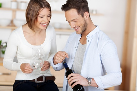Young happy couple about to drink a wine at their home photo