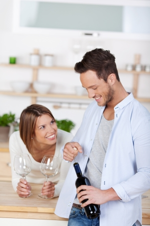 Laughing young couple starting to drink a red wine at home photo