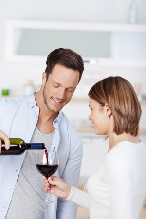 pours: Romantic couple dating and drinking red wine at home Stock Photo