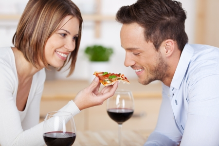 Romantic couple drinking red wine with pizza at home photo