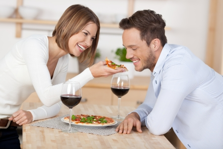 romantic dinner: Happy young couple eating pizza with red wine at the kitchen Stock Photo