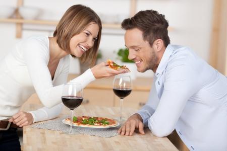 hombre comiendo: Joven pareja feliz comiendo pizza con vino tinto en la cocina Foto de archivo