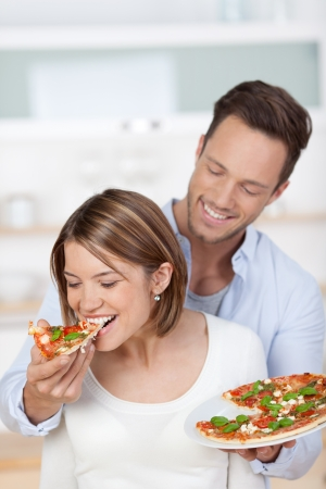 eats: Happy attractive young couple romantically eating a fresh pizza in the kitchen Stock Photo