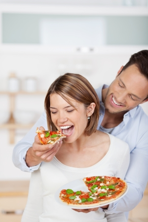 Happy cuddling couple eating pizza at their kitchen photo