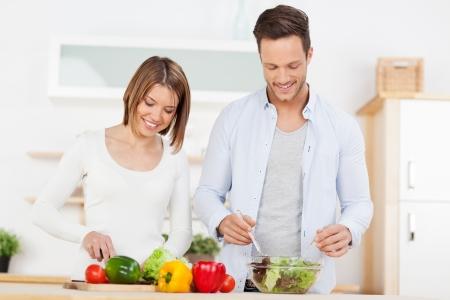 pareja comiendo: Pareja joven y atractiva que prepara la ensalada en la cocina con ingredientes frescos