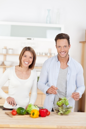 Young couple cooking in the kitchen preparing a meal using farm fresh ingredients for a salad photo