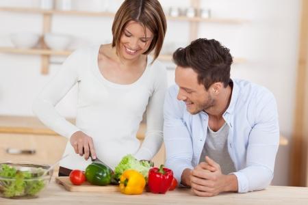 夫と妻の家に彼らの台所で野菜のサラダを準備します。
