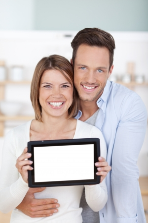 Smiling young couple holding tablet computer in a close up shot photo