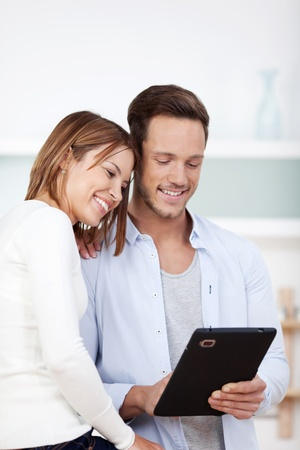 Smiling young couple browsing the internet in digital tablet at the kitchen photo