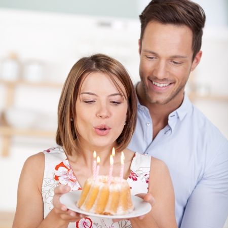 blow out: Happy woman blowing a candle on cake together with her boyfriend