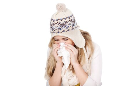 Teenage girl in knitted hat blowing her nose against white background Stock Photo - 21162562