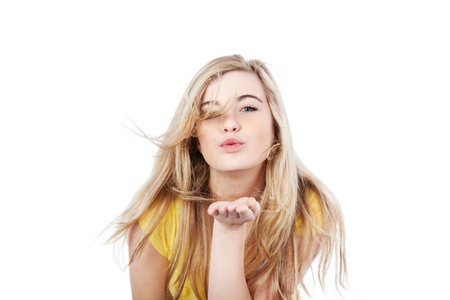 Portrait of a cute teenage girl blowing a kiss against white background