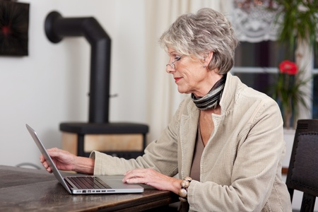 Side view of a female pensioner using laptop at home photo