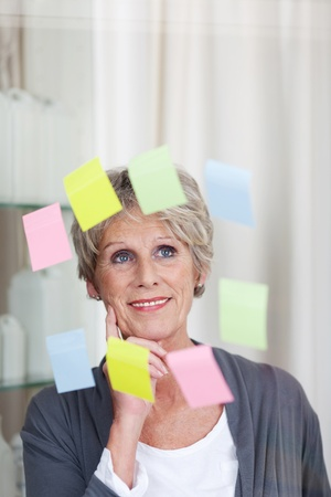 Image of modern senior woman looking at sticky notes. photo