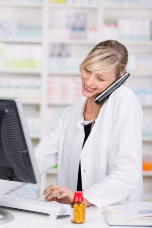 Smiling attractive female pharmacist talking at the phone and using a computer with a bottle of pills and an open book in the counter photo