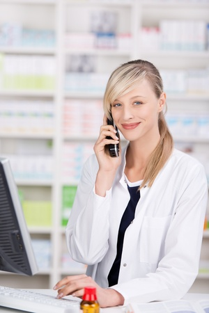 Portrait of a friendly attractive female pharmacist looking at camera while talking at the phone and using a computer with a bottle of pills and an open book in the counter photo