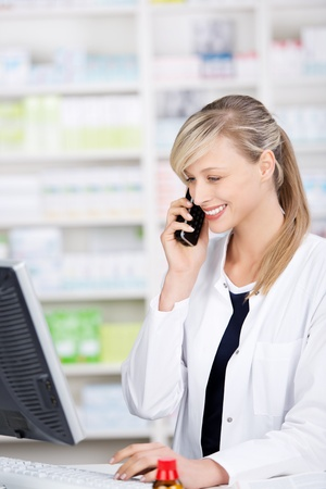 Profile portrait of a smiling attractive female pharmacist talking at the phone and using a computer photo