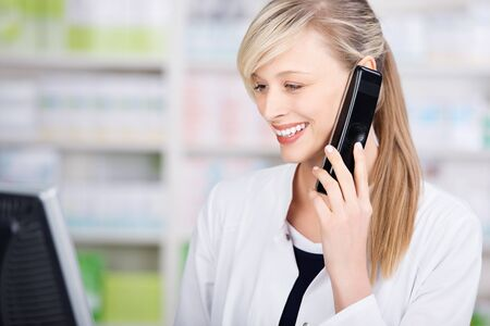 medical computer: Profile portrait of a friendly female pharmacist talking on the phone and using the computer