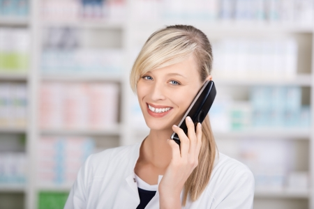 telephone saleswoman: Smiling attractive female pharmacist portrait on the phone looking at the camera Stock Photo