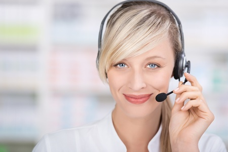 phone operator: Portrait of a friendly female pharmacist looking at camera using headsets and holding the microphone